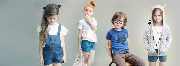 Bambini posano con alcuni abiti in vendita su Smallable